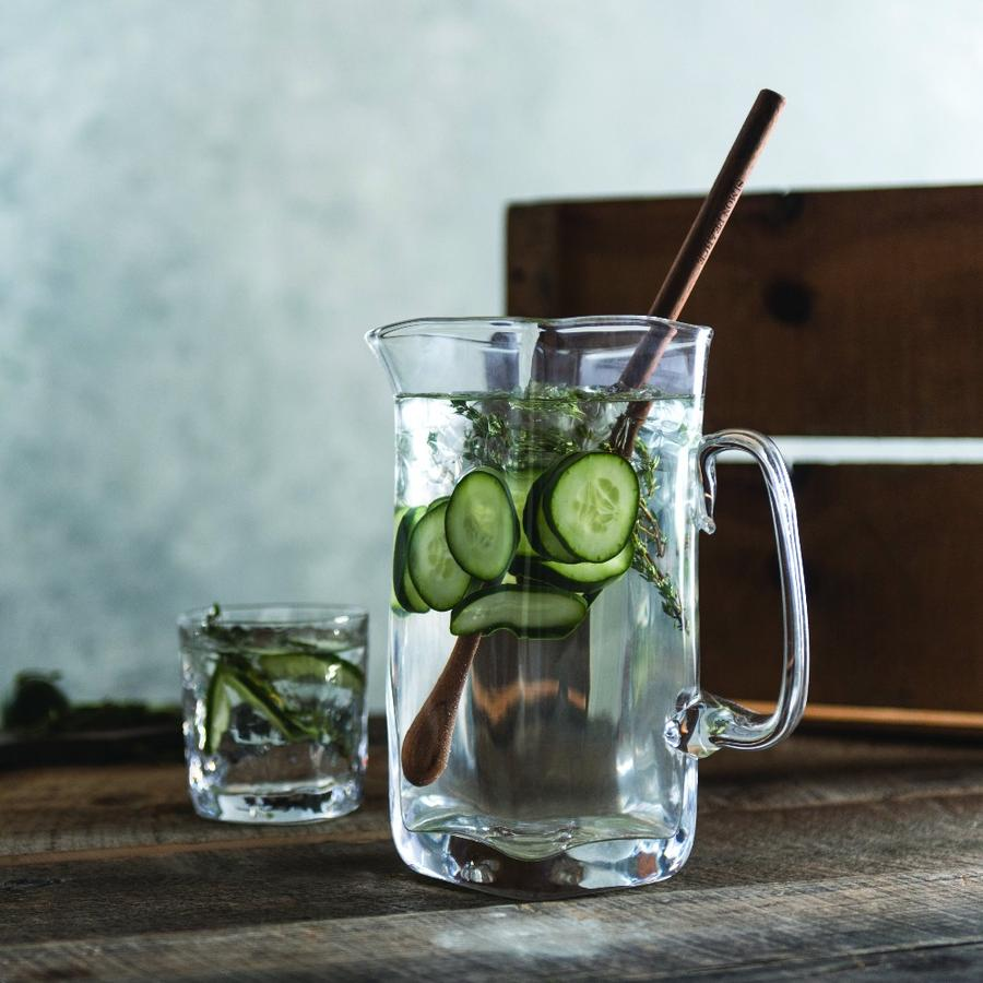 A glass pitcher filled with cucumber water